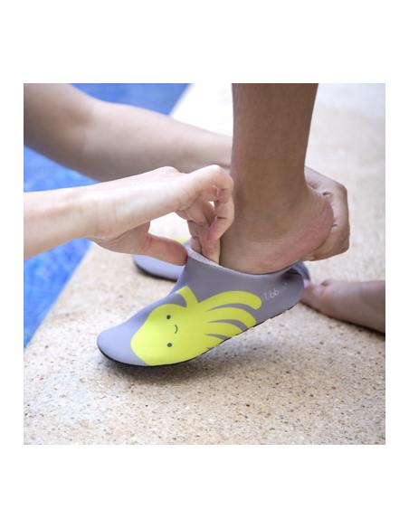 Calzado de baño Shoöz en neopreno Gris. Niño poniéndose los zapatos de agua de color gris y verde.