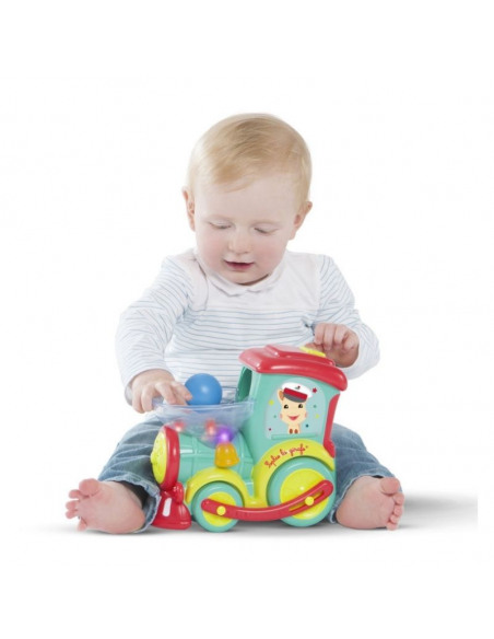 Tren Magik Pop Sophie la girafe. Bebé rubio con una camiseta blanca jugando pone las bolas en el recipiente del tren.