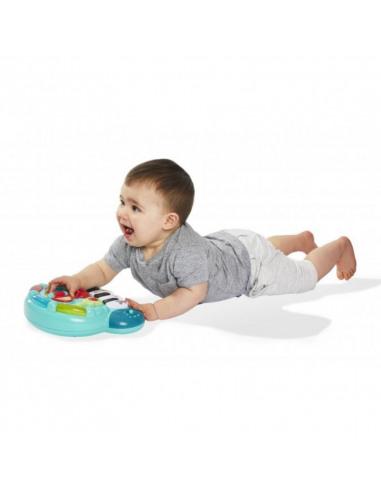 Piano' folies Sophie la girafe. Bebé tumbado con pelo castaño, camiseta gris tumbado jugando con el piano.