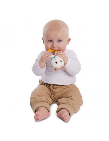 Sonajero peluche anillo de dentición. Bebé rubio con camiseta blanca y pantalón marrón mordiendo el sonajero