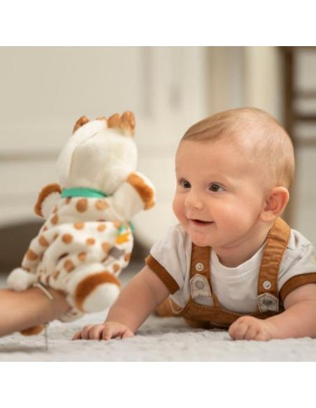 Doudou Marioneta Sophie. Bebé mira fijamente a la marioneta de peluche con forma de jirafa