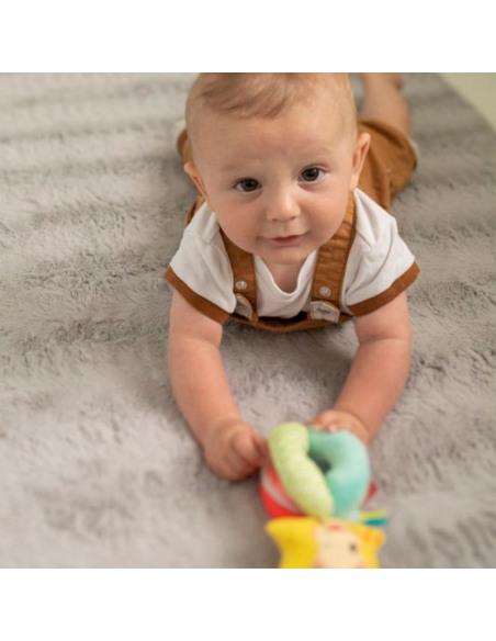 Sonajero bolitas. Bebé tumbado con ropa blanca y marrón sostiene el sonajero