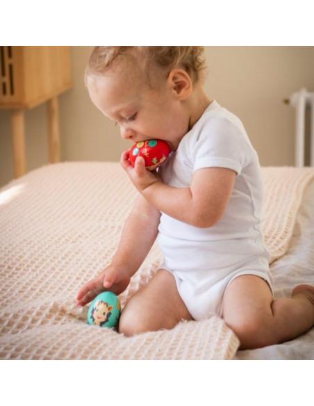 Egg shakers - Tentetieso/Maracas. Bebé muerde dos huevos de juguete de color rojo y azul