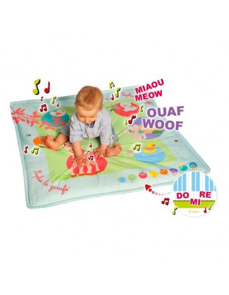 Touch & play mat'. Bebé pulsando los botones de la alfombra de juego musical de color azul y con dibujos de Sophie la girafe