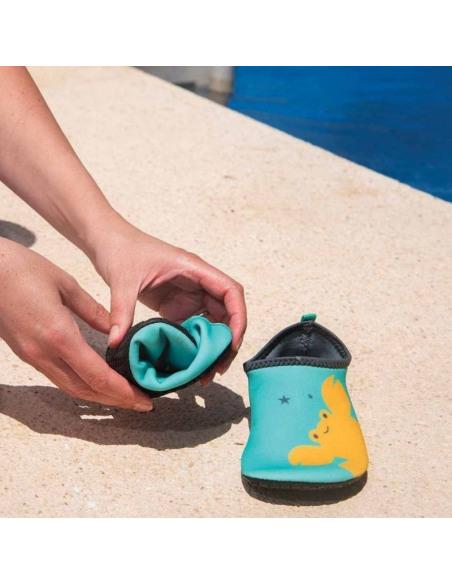 Calzado de baño Shoöz en neopreno Aqua. Manos cogiendo los zapatos de agua de color azul y amarillo.