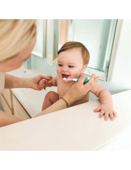 Bebé y su madre usando el cepillo de dientes de color azul y blanco.