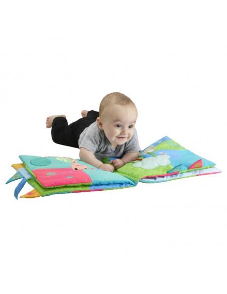 Mi primer libro de los sentidos Gigante Sophie la girafe. Niño tumbado leyendo con el libro extendido.