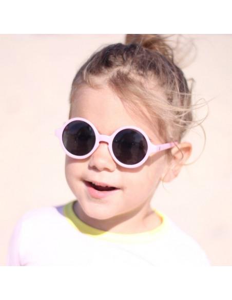Niña rubia con gafas de sol de color rosa.