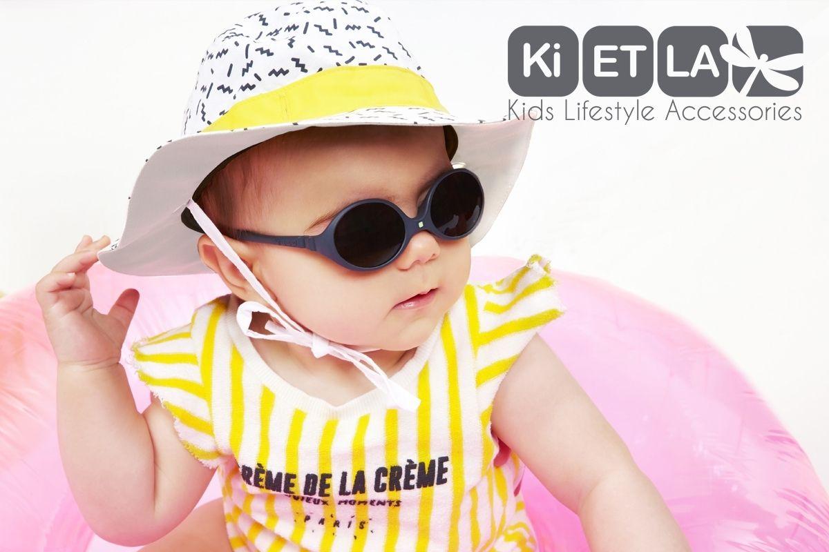 Bebé con gafas de sol negras y gorro amarillo de Ki ET LA.